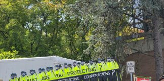 """Background with board figures of police in uniform with words """"what are you protecting?"""" on top and """"the environment or destructive corporations?"""" at bottom. Foreground is people facing the right side."""