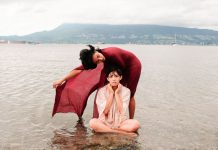 Chantal, in character, sits cross-legged in the ocean while Anjalica stands behind them, one arm outstretched protectively