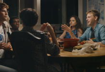 A group of friends mid-conversation, sitting around a dinner table