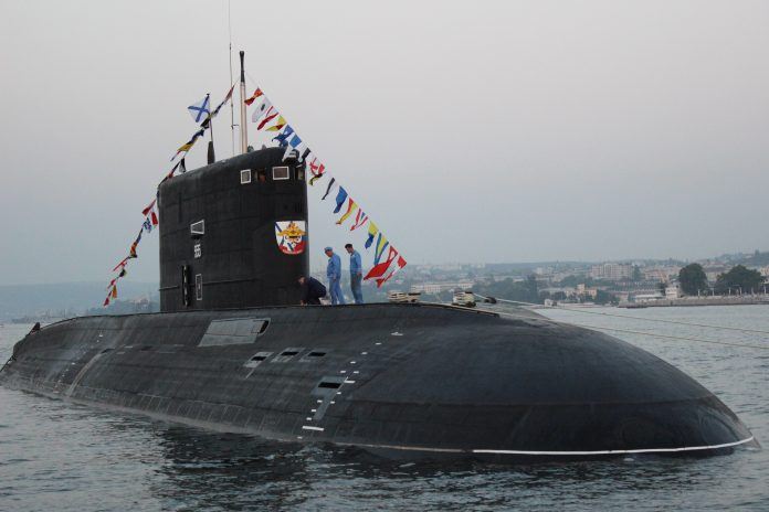 A partially submerged black submarine has two people standing on top. The submarine is near shore and the top has many countries' flags flown.