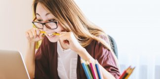 Woman holds and bites pencil staring at laptop screen.