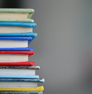A stack of textbooks against a blurred grey background